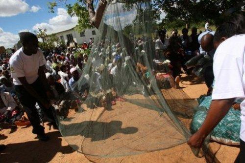Des militants associatifs posent une moustiquaire au Zimbabwe en février 2009 pour protéger la popul