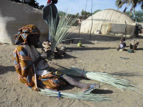 Frau beim Flechten einer Matte