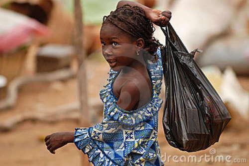 Jeune fille africaine marchant avec un sachet en plastique noir.