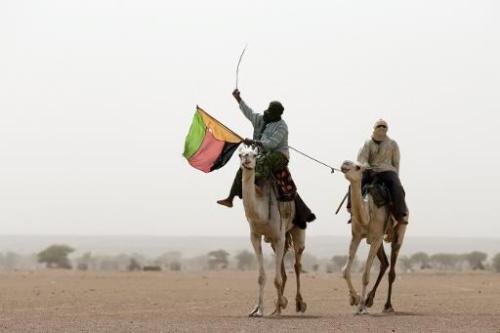 Un Touareg brandit le drapeau du MLNA, à Kidal, dans le nord du Mali, le 28 juillet 2013