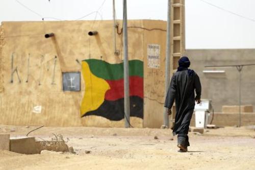 Un homme passe à côté d'un drapeau peint sur un mur du Mouvement national pour la libération de l'Az