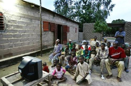 Des habitants de Baramba, au Mali, regardent la télévision