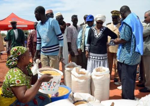 Ertharin Cousin (4th R), director of the UN World Food programme, watches food being distributed at