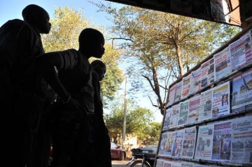 Des habitants regardent des Une de journaux à Bamako, au Mali