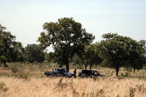 Des gendarmes examinent le site d'une fosse commune où les corps de 21 soldats ont été r