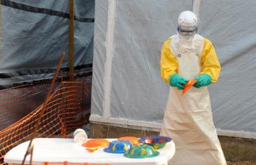 Un médecin en tenue de protection désinfecte les assiettes de patients, dans le centre d