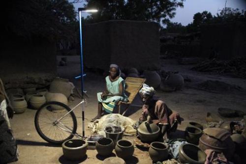 Des femmes s'éclairent avec un lampadaire solaire à Dona, dans la région de Segou, le 25