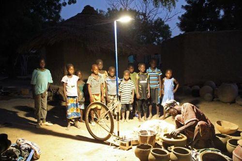 Des enfants regardent des femmes sculpter des poteries sous une lampe solaire à Dona, da