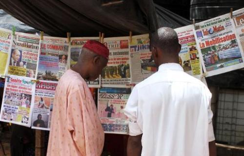 Des Maliens lisent les quotidiens titrant sur la défaite de l'armée malienne dans une ba