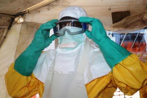 Un membre de Médecins Sans Frontières s'équipe de vêtements de protection pour entrer dans une zone