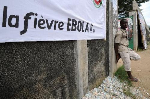 Un homme adossé à un mur près d'une banderole destiné à mobiliser la population dans la lutte contre