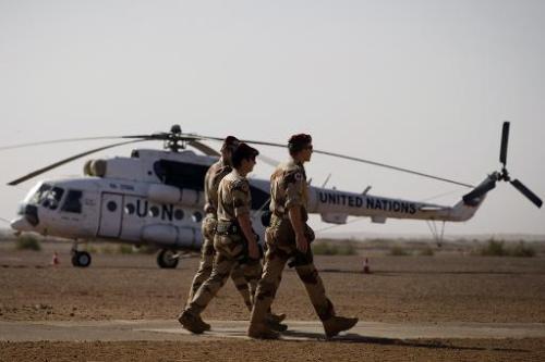 Des soldats français passent le 31 décembre 2013 devant un hélicoptère de l'ONU, sur la