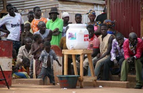 Des habitants de Kouremale près d'un bidon pour se laver les mains, lors de l'épidémie d