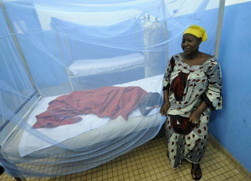 Une femme devant le lit de son enfant malade allongé sous une moustiquaire dans un hôpital d'Abidjan