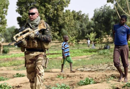 Un soldat français de l'opération Barkhane patrouille près de lopins de terre cultivés a